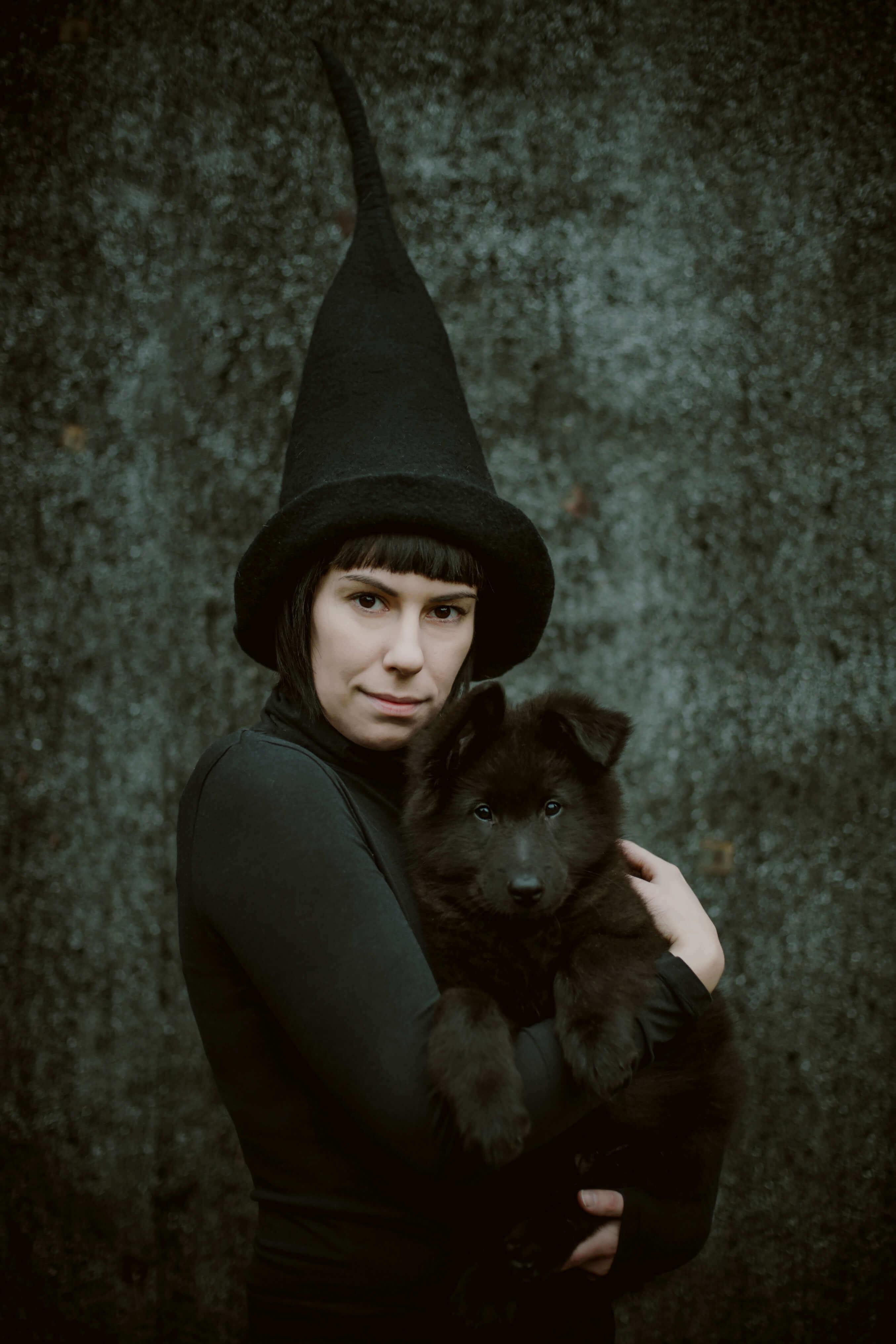 dziewczyna z czarnym psem w czapce wiedźmy