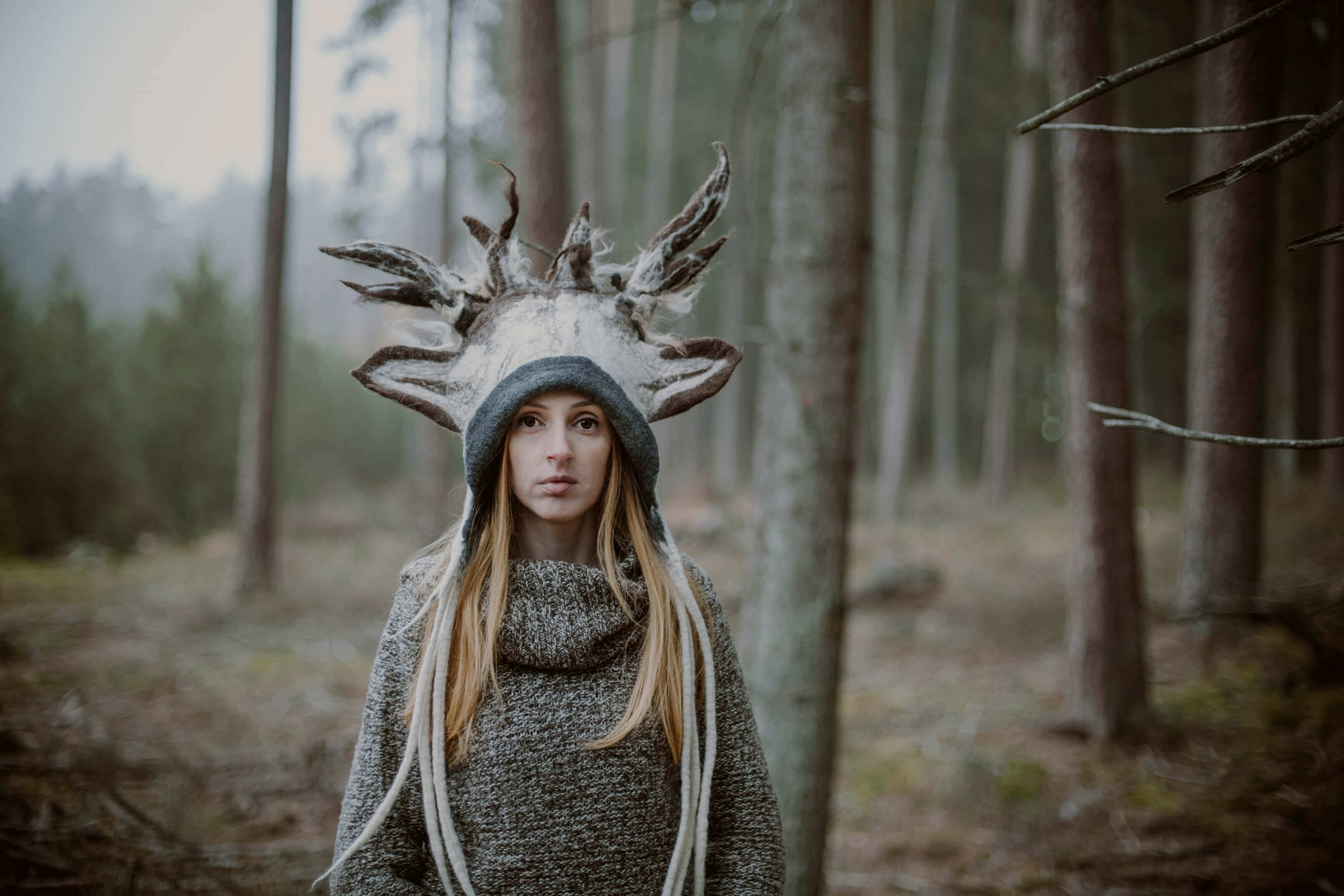 dziewczyna w czapce jelenia w lesie